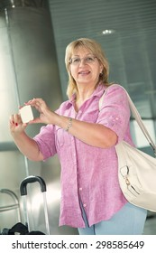 Adult woman smiling and talking on a smart phone. Happy woman her cell phone. Traveler with mobile phone in airport. Tourist woman with travel bag. Take photos on your mobile phone.