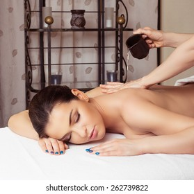 Adult woman in spa salon having body relaxing massage, lying on table, with olive