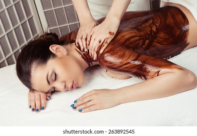 Adult woman in spa salon having body relaxing massage, lying on table, with chocolate olive