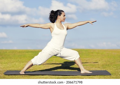 An adult woman standing on a black yoga mattress in the Virabhadrasana II (aka warrior II) pose, on a green lawn with cloudy blue sky in the background.