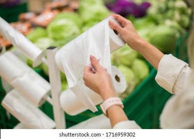 Adult woman taking one plastic package from the roll of packing plastic bags in the vegetable department of the supermarket or grocery store