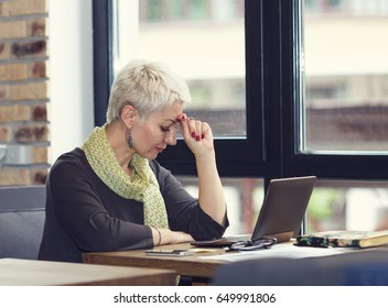 Adult woman thinking about to complete work task. Tired woman working at office desk in front of laptop suffering from chronic daily headaches from computer. Frustrated woman.