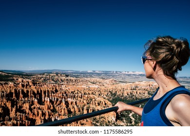 Adult woman tourist wearing a tank top with sunburned skin looks out at the view of hoodoos of Bryce Canyon National park at Inspiration Point. Utah, USA