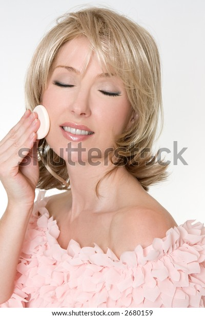 An adult woman using a cosmetic sponge to begin removing makeup.