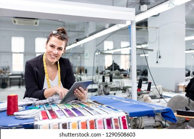 Adult woman using digital tablet in factory.