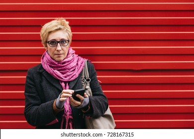 Adult woman using smartphone standing at red fence on city street.
