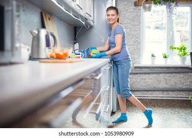 adult woman washes dishes at home in the kitchen in the sink