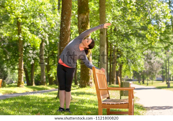 Adult woman wearing sportswear stretching in park on sunny day