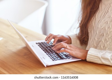 Adult woman wearing warm sweater and working at home one autumn day