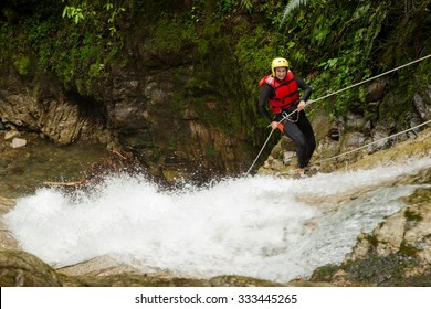 Adult Woman Wearing Waterproof Equipment Descending A Waterfall