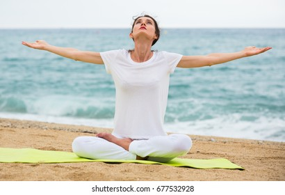 Adult woman in white T-shirt is sitting and practicing asana on nature.