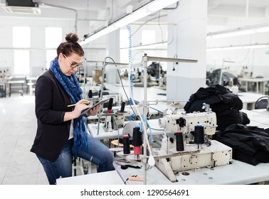 Adult woman working with digital tablet in factory.