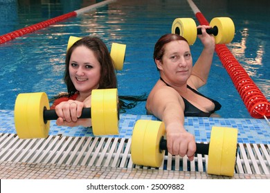 A adult women and young woman in water with dumbbells