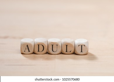 Adult word on wooden cubes. Adult concept