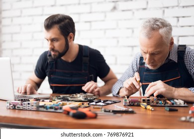 Adult and young men repair parts from the computer together. They are in a repair shop. They use different tools.