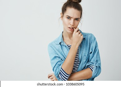 Adulthood hit me unexpectedly. Studio shot of bothered and puzzled attractive woman in bun hairstyle, biting thumb while frowning and looking serious at camera, being worried about something