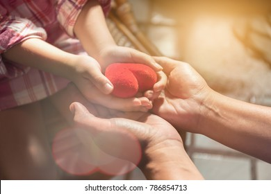 Adults and children are holding a red heart.Happy family relationships and health care concept.