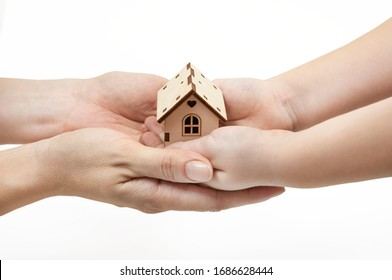 adults and children's hands holding a wooden house, family home, homeless housing and home insurance concept, international family Day, foster care, on a white background.