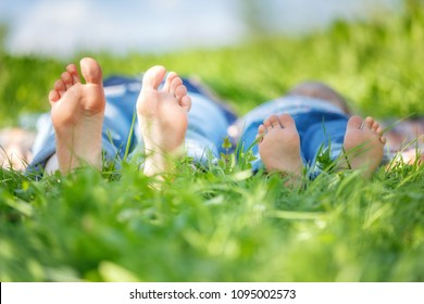 Adult's and child's bare feet on green summer grass