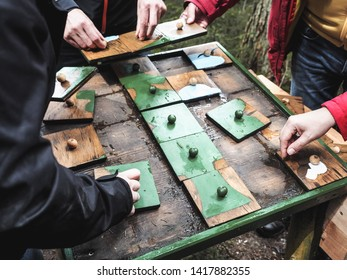 Adults putting together pieces of outdoor wooden puzzle. Forest of Senses (Wald der Sinne), educational  walk in Altenberg. Styria, Austria, May 20, 2019.