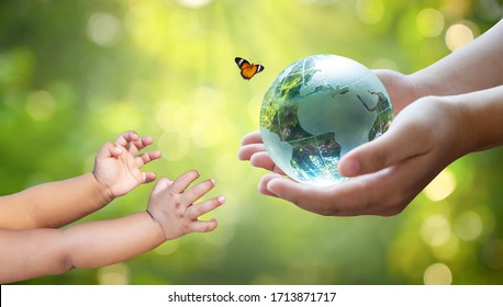 Adults are sending the world to babies. Concept day earth Save the world save environment The world is in the grass of the green bokeh background