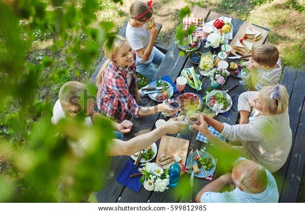 Adultes dégustant des lunettes de vin à table servie en famille