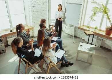 Advanced. Female speaker giving presentation in hall at workshop. Business centre. High angle view of participants in audience. Conference event, training. Education, diversity, inclusive concept.