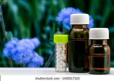 Advanced Homeopathic Concept - Close up image of homeopathic globule sugar pills and liquid substance in glass bottle with blurred blue flower and green leaves background
