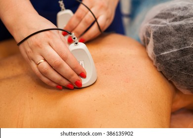 Advanced medical therapy with device for treating pain in back for female in Spa Salon done by Beautician Specialist in close