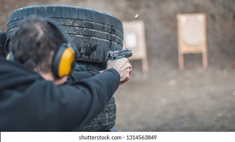 Advanced outdoor tactical shooting on target around barrier and wall. Civilian firearm safety training on shooting range