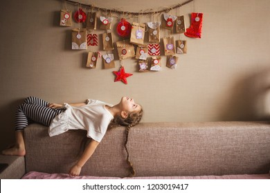 the advent calendar hanging on the wall. small gifts surprises for children. girl lies and looks at the calendar.