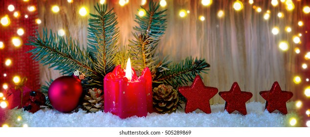 Advent candle and red Christmas decoration .