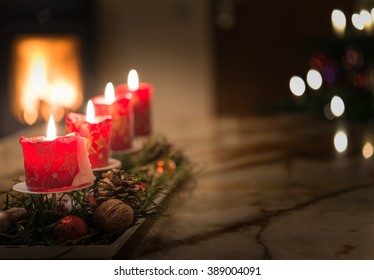 Advent candles with Christmas tree and burning chimney fire