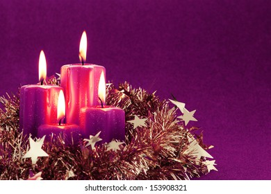 Advent candles with gold tinsel and copy space