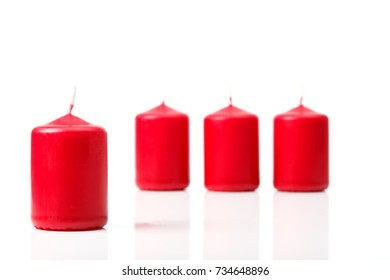 Advent candles in red, first in front, set of four to be lit on the Sundays leading up towards Christmas, isolated on white background.
