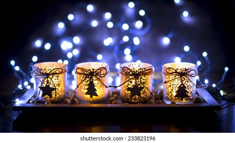 Advent, four candles decorated Christmas tree on a background of lights