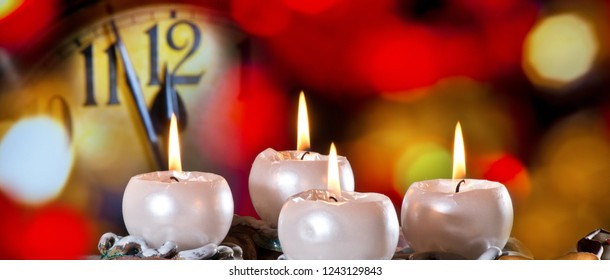 Advent Wreath with Burning Candles in  front of New Year Clock