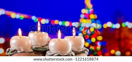 Advent Wreath with Burning Candles in  front of Christmas Tree