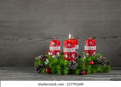 Advent wreath or crown with four red candles on wooden background.