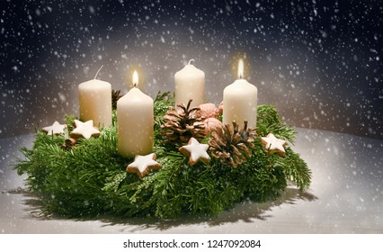 Advent wreath from evergreen branches with white candles, the second is burning for the time before Christmas, dark snowy background with copy space, selected focus