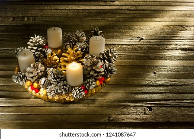 advent wreath with first burning candle on rustic old wooden table