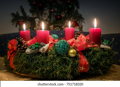 advent wreath with four lighted red candles, handcrafted christmas decoration at home