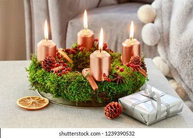 Advent wreath made of moss, cinnamon sticks and rosa canina twigs.