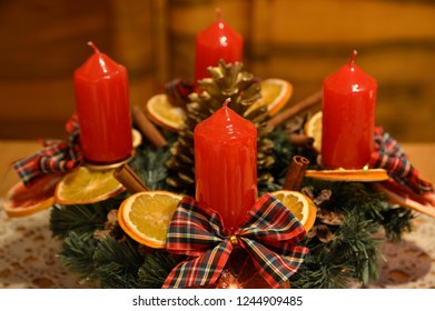 advent wreath with red candles, dried slices of oranges, golden pine cone and  red caro bows