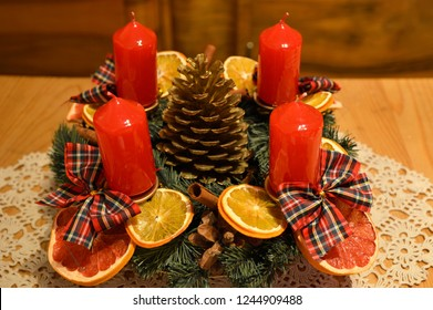 advent wreath with red candles, dried slices of oranges, golden pine cone and  red caro bows  at the wooden table