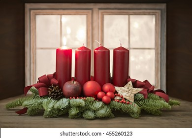 Advent wreath with red candles in front of a window