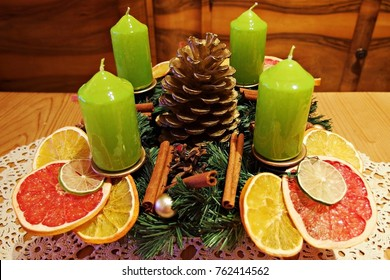 advent wreath at the table with dried oranges and green candles close up