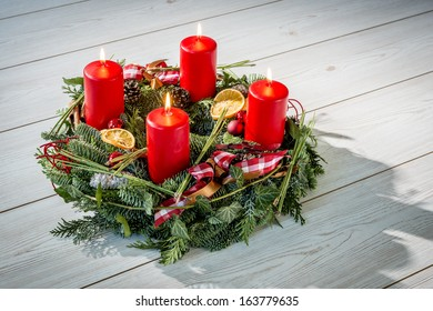 Advent wreath of twigs with four burning red candles and various ornaments