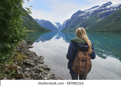 Adventure backpacking woman enjoying view of majestic mountain lake explore travel discover beautiful earth