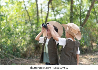 Adventure boys are using a binocular while they travel the jungle.